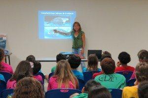 La bióloga del DRNA, Nilda Jiménez, ofrece una charla a estudiantes de quinto grado.