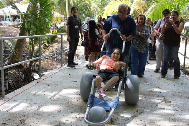 María López, inicia el recorrido de una vereda de la Reserva Natural Punta Tina, en Maunabo,  en una de las sillas especiales acompañada de su abuelo.