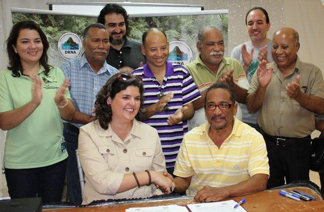 La secretaria del Departamento de Recursos Naturales y Ambientales (DRNA), Carmen R. Guerrero Pérez, firma un acuerdo colaborativo con el representante de la incubadora de microempresas Inciativa de Eco Desarrollo de Bahía de Jobos (Idebajo), Nelson Santos, para establecerse en la Reserva Nacional de Investigación Estuarina de Bahía de Jobos (JBNERR).