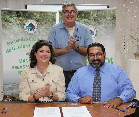 La secretaria del Departamento de Recursos Naturales y Ambientales (DRNA), Carmen R. Guerrero Pérez, firma un acuerdo colaborativo con Israel Guzmán y Javier Biaggi, de la Sociedad Ornitólogica de Puerto Rico (SOPI), para iniciativas educativas, de interpretación y ecoturísticas en el Bosque estatal de Cambalache.