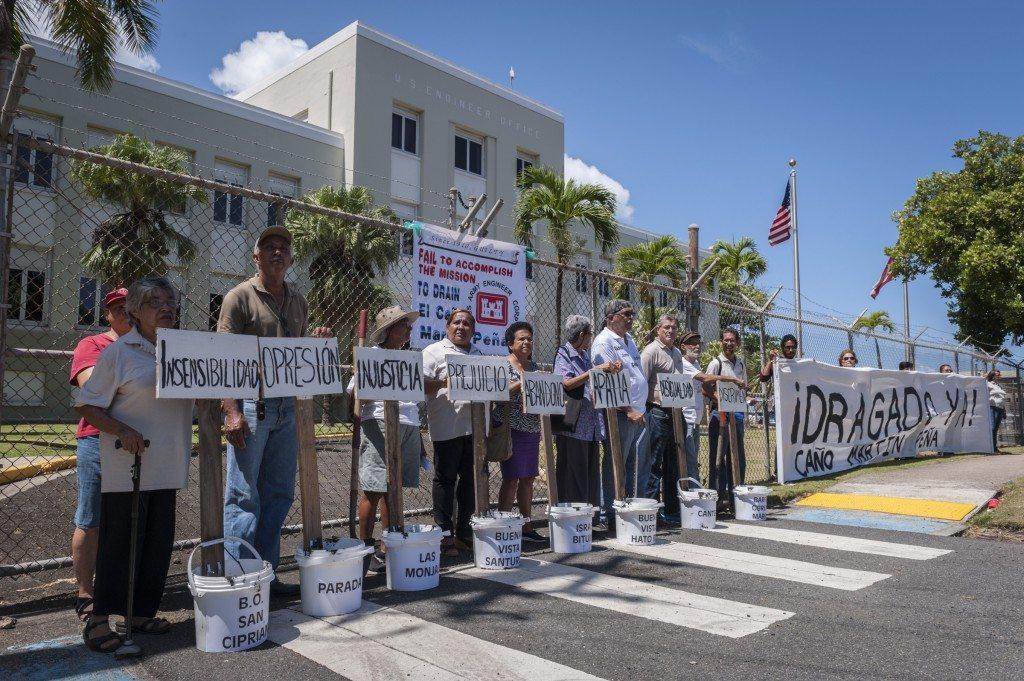"""El grupo se movilizó frente a la sede de la entidad federal en Puerta de Tierra para llevar ocho pailas de material contaminado, cada una rotulada con el nombre de una comunidad y palabras como """"injusticia"""", """"prejuicio"""" e """"insensibilidad"""". (suministradas)"""