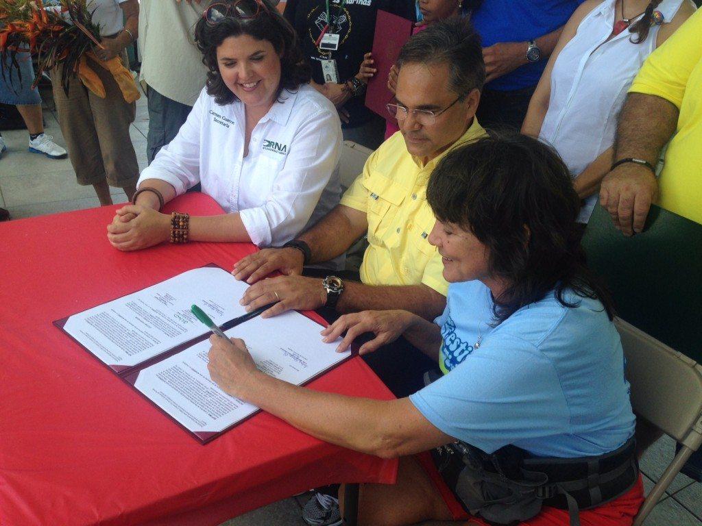 Momento de la firma del acuedo de colaboración y trabajo entre el DRNA y la organización comunitaria. (suministrada)